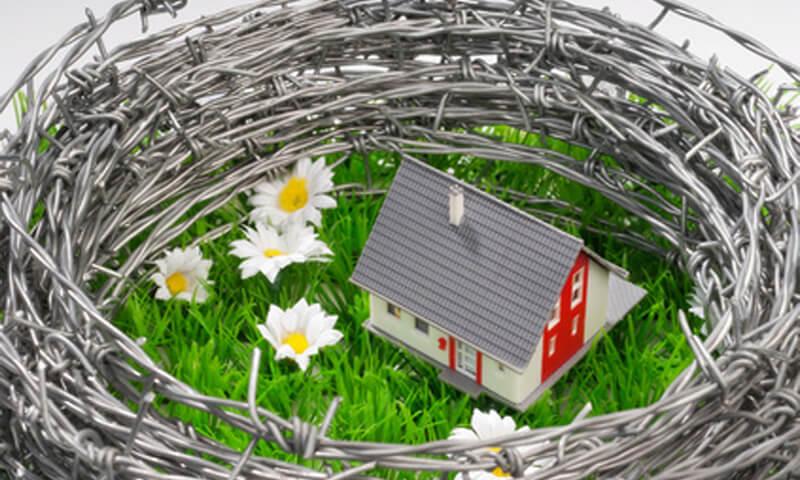 Haus mit Zaun aus Stacheldraht