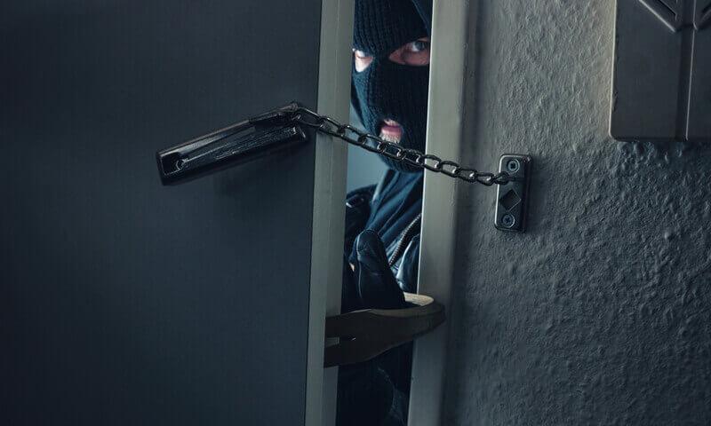 Einbrecher schaut durch Türspalt
